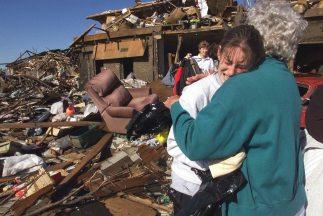 Dos mujeres de abrazan junto a los escombros de una vivienda totalmente...