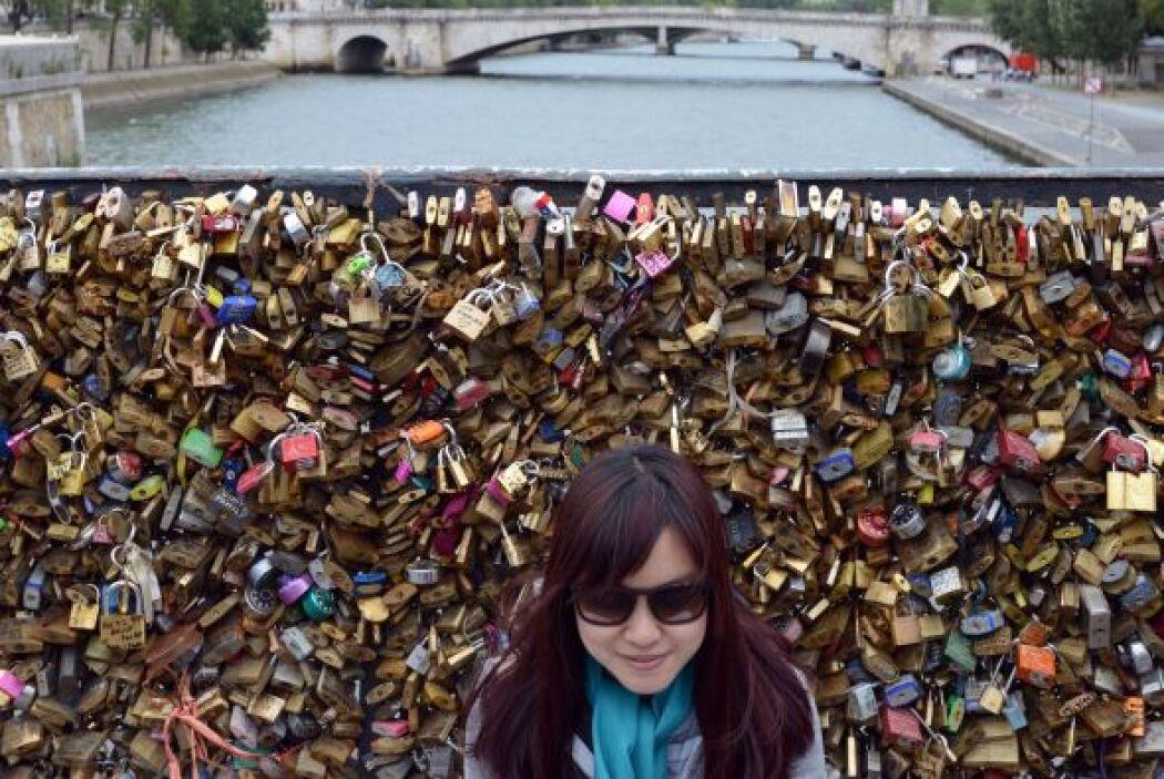 Lili, una turista de Macao posa frente al Puente de las Artes en Francia.