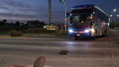 Un autobus de pasajeros pasa al lado de una alcantarilla abierta, luego...