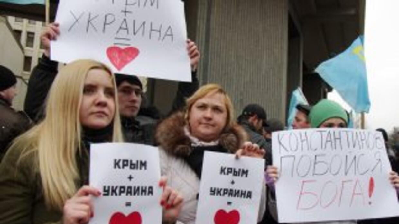 """Activistas pro-ucranianas sostienen pancartas con la consigna """"Crimea +..."""