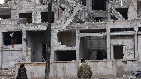 Soldados miran un edificio de Alepo destruido por los bombardeos
