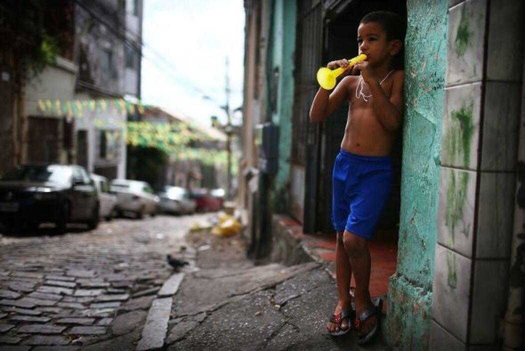 Un niño brasileño toca una trompeta en las calles de Brasil.