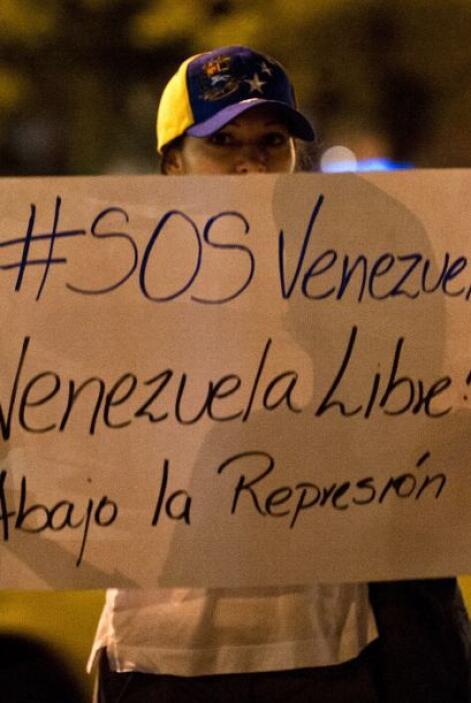 Opositores al gobierno portan una pancarta en la que piden salvar a Vene...