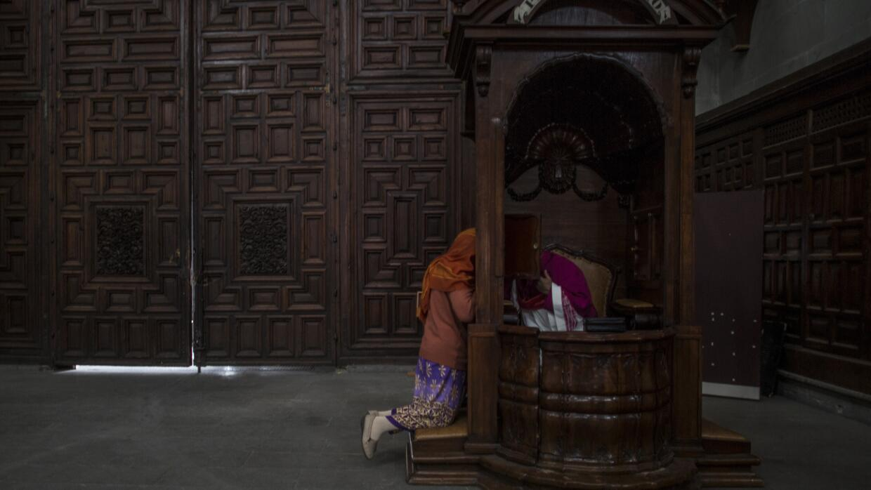 Un religioso confiesa a una fiel en Ciudad de México