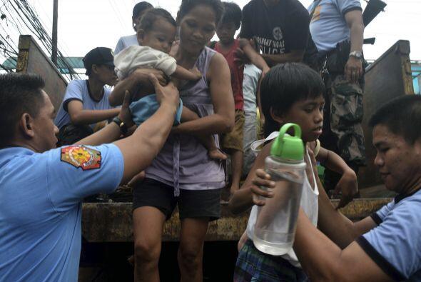 Varios de los rescatados que son ayudados por voluntarios. (AP)