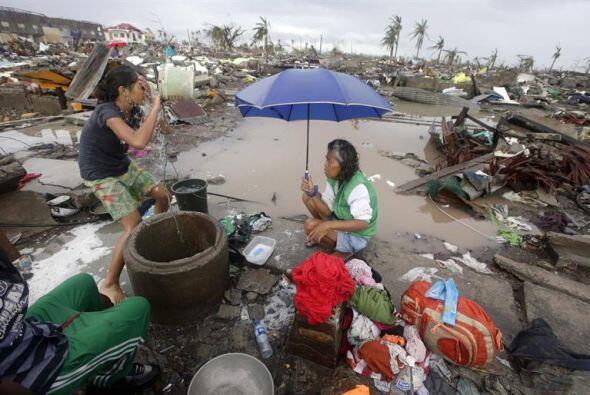 Una mujer filipina lava su ropa en medio de la devastación dejada por el...