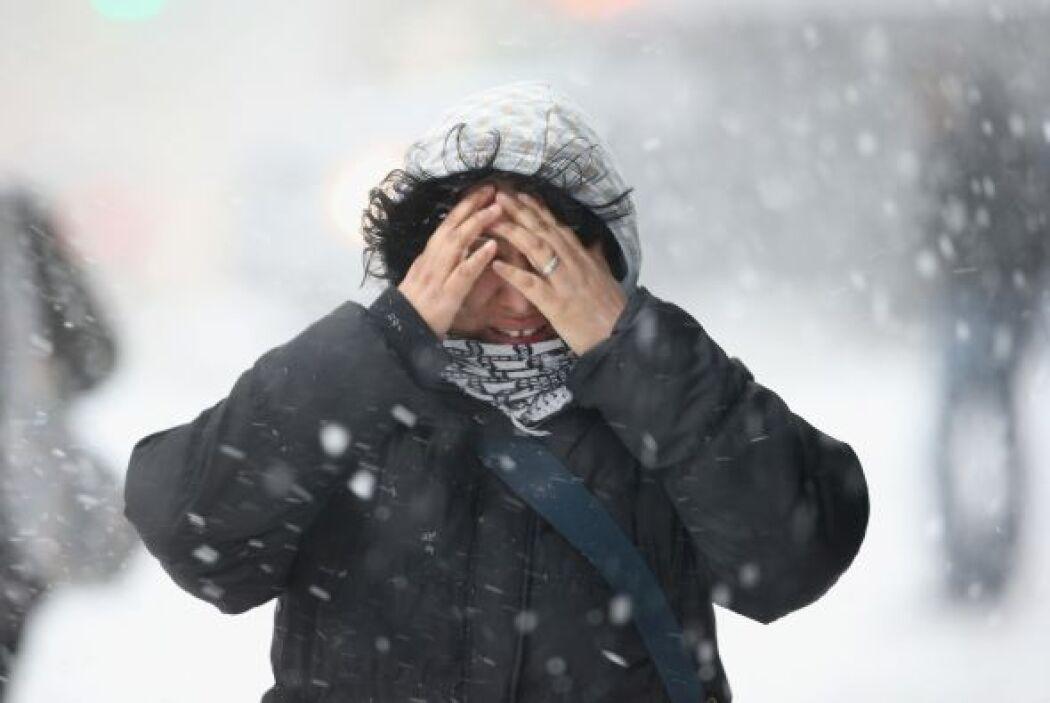 Una mujer se cubre el rostro en Nueva York mientras ca mina por una call...