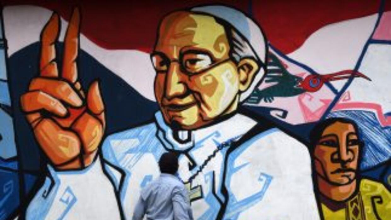 Un hombre observa un mural con la figura del papa Francisco en una calle...