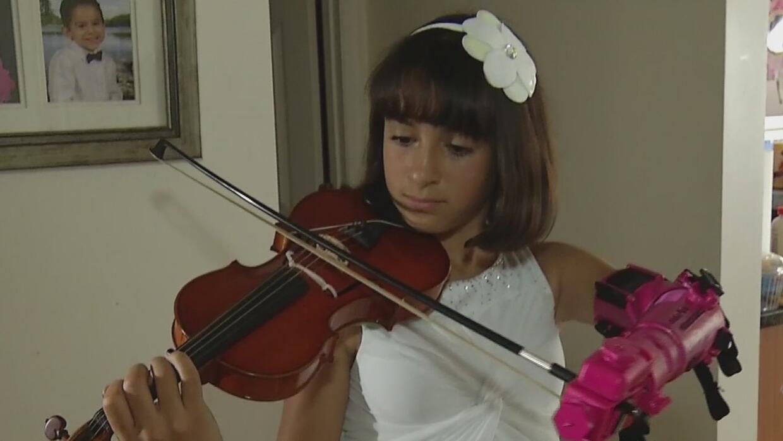 La niña sin antebrazo que toca el violín con una prótesis en 3D hecha po...