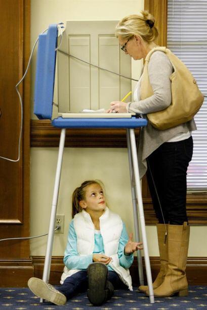 Ella Duane espera impaciente a que su madre, Laura Duane, emita su voto...
