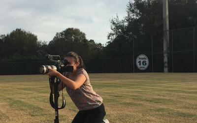 Laura Prieto filming on the baseball field at Alonso High School where J...