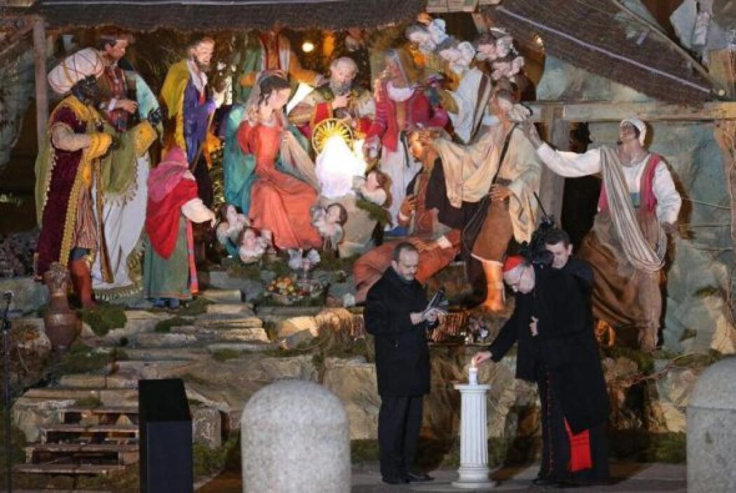 El cardenal Angelo Comastri enciende una vela junto al pesebre de Belén...