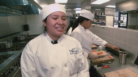 Estudiante hispana de cocina prepara la comida para los fanáticos del Su...