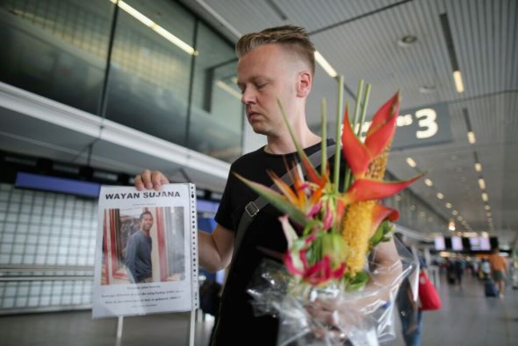 El holandés Arthur Laumann porta una ofrenda floral junto con la fotogra...