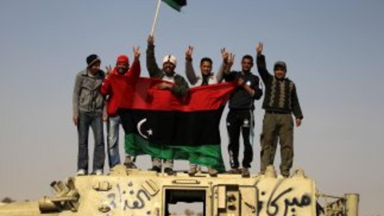 Rebeldes libios celebran sobre un tanque de las tropas del coronel Muama...