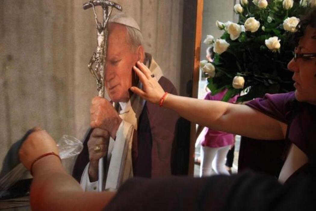 Fieles oran ante una imagen del papa Juan Pablo II, en la explanada de l...