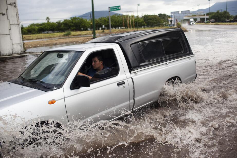 Un carro avanza por una calle inundada de Tecomán, Colima.