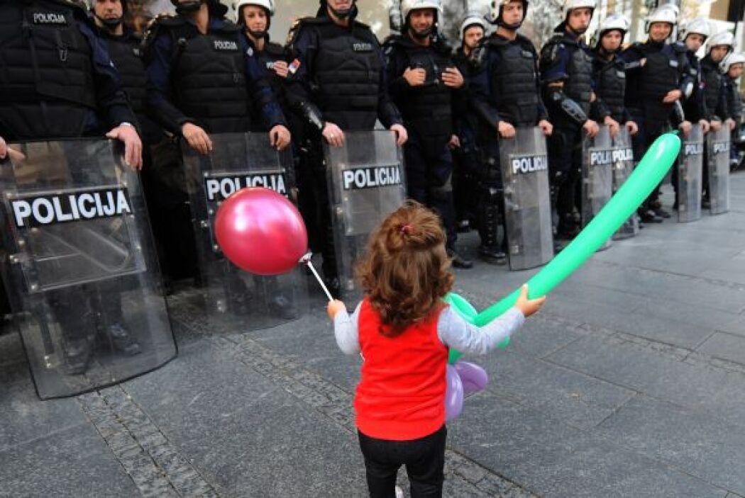Esta pequeña estremece al sostener unos globos frente a policías antidis...