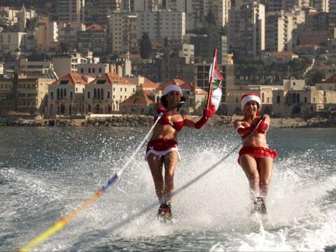 Dos mujeres libanesas vestidas de Santa Claus ondean la bandera nacional...