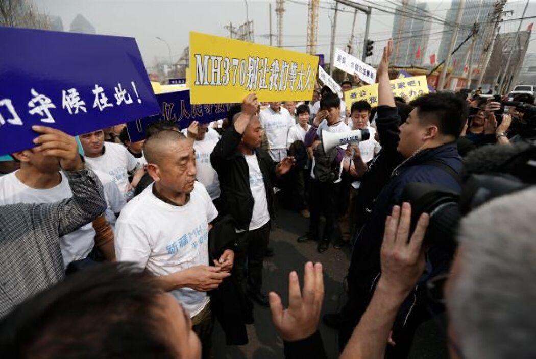 Los familiares de los pasajeros del vuelo MH370 protestaron frente a la...