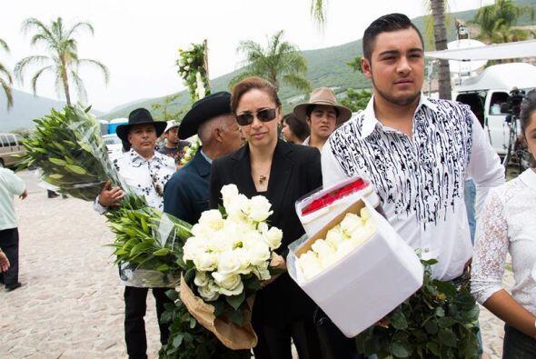 Aquí seguidores con famos de flores para rendirle homenaje a su artista.