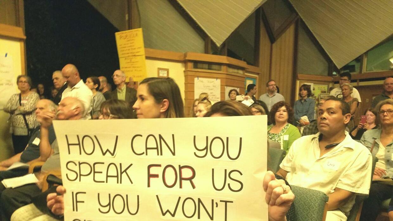 Asistente a la asamblea en la que faltó Rubio porta un cartel que dice:...