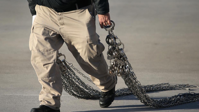 Un agente federal de ICE transporta grilletes y cadenas que utilizan par...