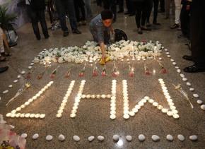 Un miembro de la tripulación de Malaysia Airlines deposita una vela