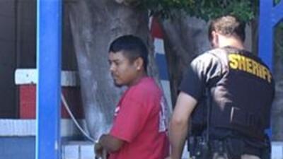 Las redadas continuan - agente del sheriff deteniendo a un inmigrante