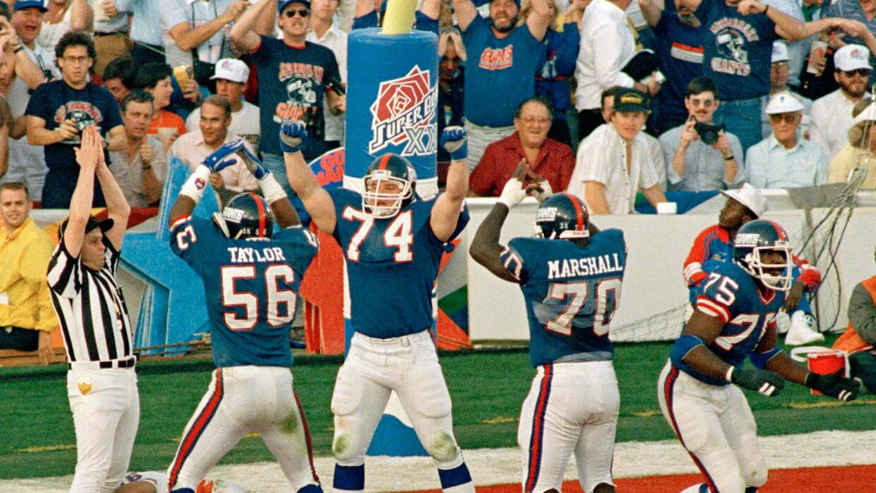 Erik Howard (74) y Lawrence Taylor (56) capturaron a John Elway en el  S...