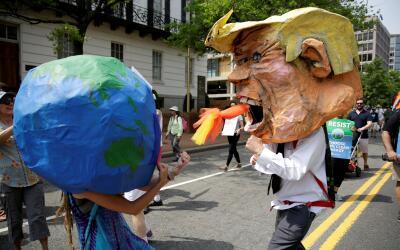 Manifestantes vestidos como la Tierra y el presidente Donald Trump finge...