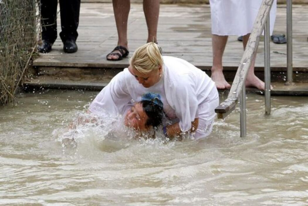Una madre y su hijo se sumergen en el agua con objeto de bautizarse en e...