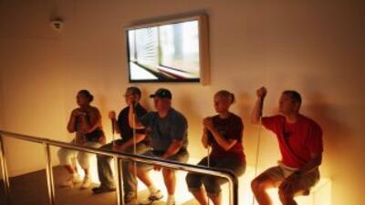Un grupo de personas son guiadas a través de la exhibición. Todos usan e...
