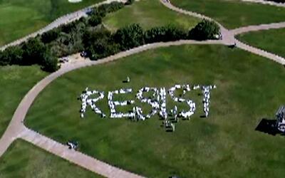 Al menos 200 manifestantes formaron la palabra resist en Trump National...