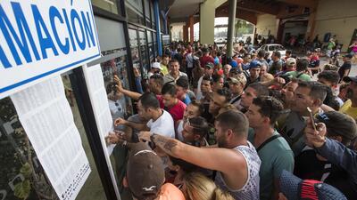 Un grupo de cubanos busca información en las primeras listas de c...