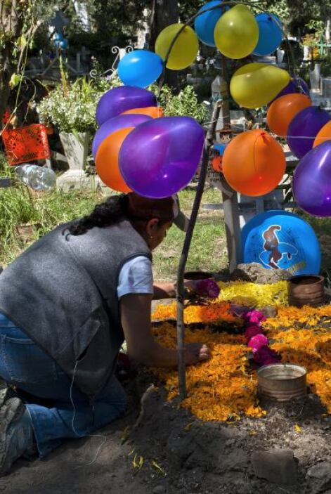 Los familiares de los difuntos cubren las tumbas de flores y adornos, qu...