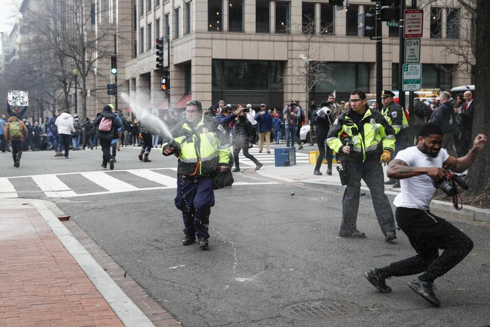 Oficiales de policía repelen a los manifestantes con gas pimienta en una...