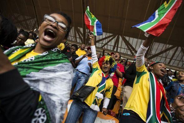 Varios sudafricanos cantan y bailan bajo la lluvia mientras ocupan el es...