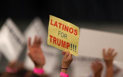 Una mujer sostiene un cartel de apoyo a Trump en un mitin en California