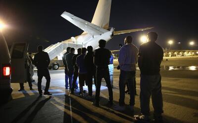 Inmigrantes indocumentados esperan para subirse a un avión de ICE.