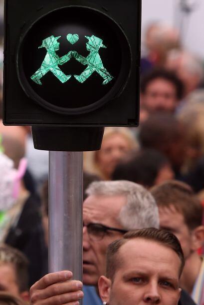 Un hombre sostiene un semáforo peatonal con una luz verde y dos hombres...