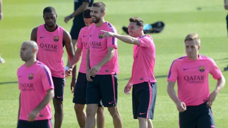 Messi, con nuevo look, bromea al lado de Piqué y otros jugadores.