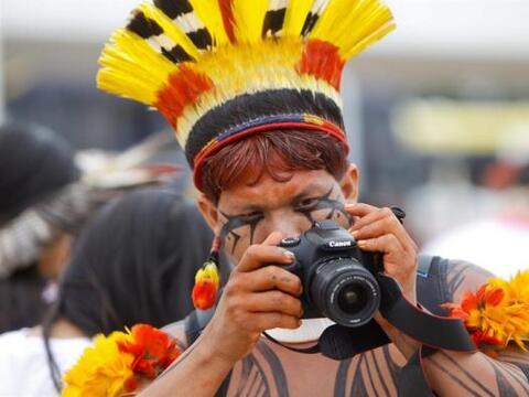 Un indígena brasileño toma fotos durante una protesta por...