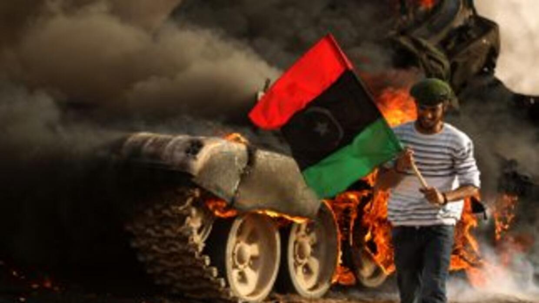 Un rebelde libio agita una bandera después de tropas aliadas destruyeran...