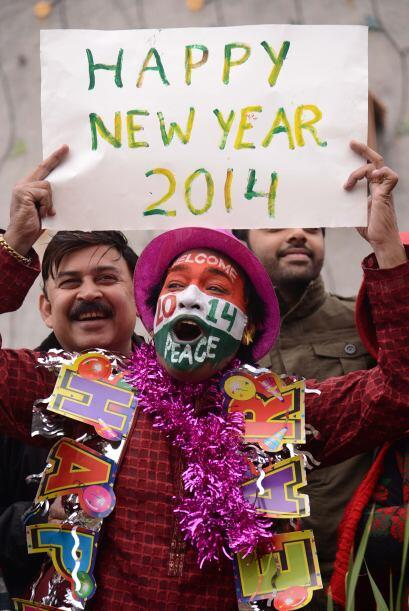 En India un hombre porta un cartel para darle la bienvenida al 2014.