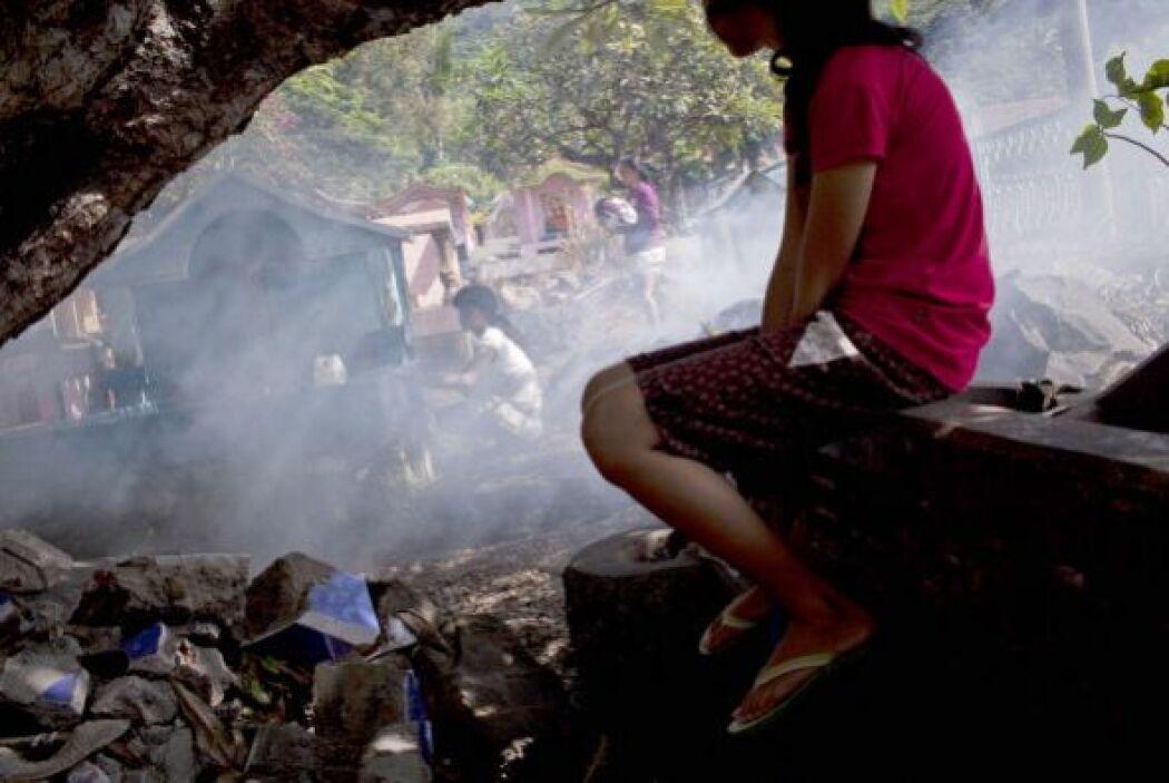 Los indonesios celebran limpiando las tumbas de sus antepasados durante...