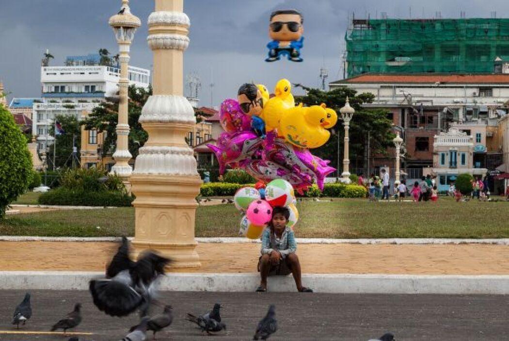 Un niño vendedor de globos se sienta a mirar a las palomas frente al Pal...