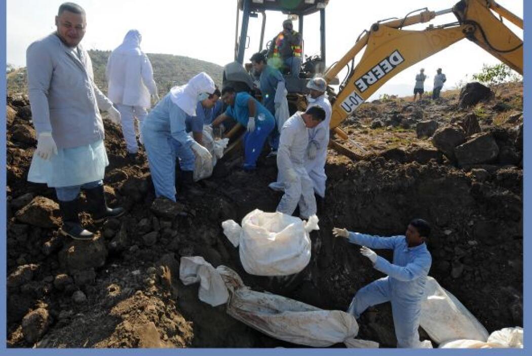 Con una pesada máquina excavadora, los empleados de la Morgue Judicial d...