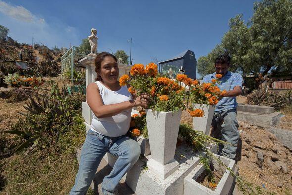 Además de las flores, algunas familias llevan a las tumbas objeto...