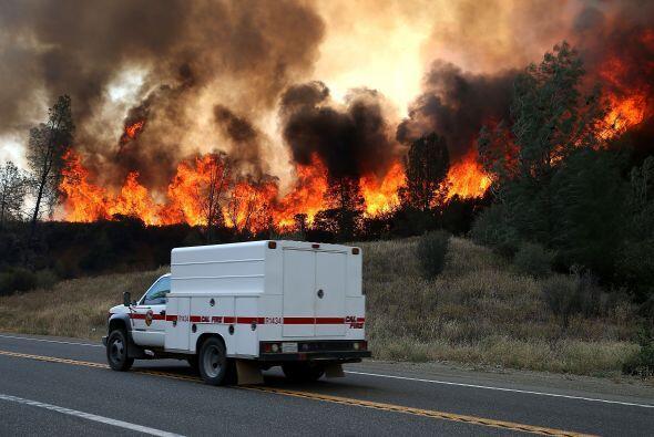 Las llamas arden detrás de un vehículo.